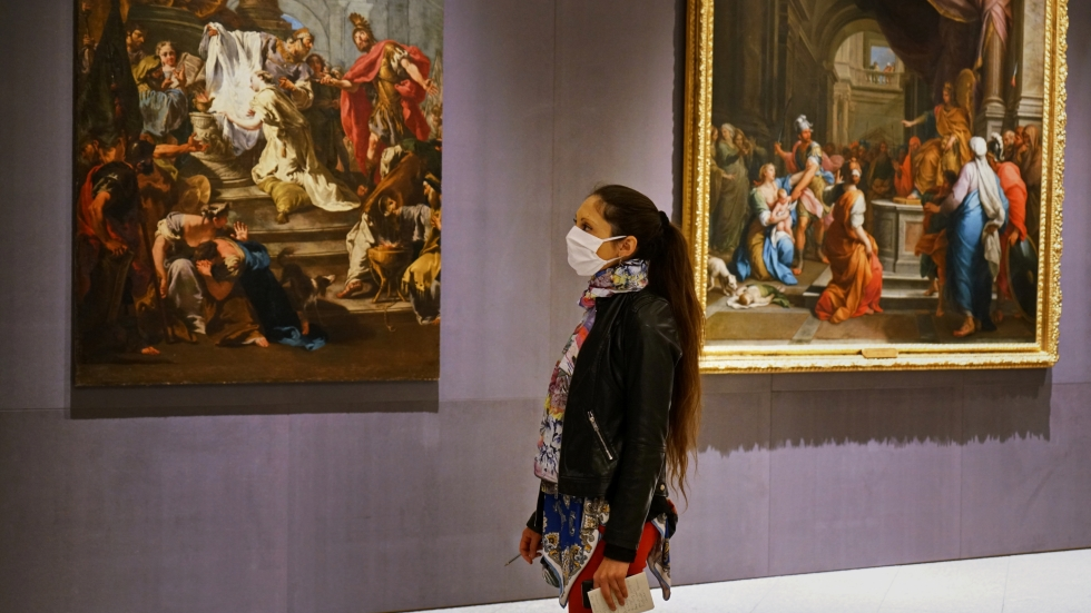A museum visitor in Turin, Italy, look at the artworks.