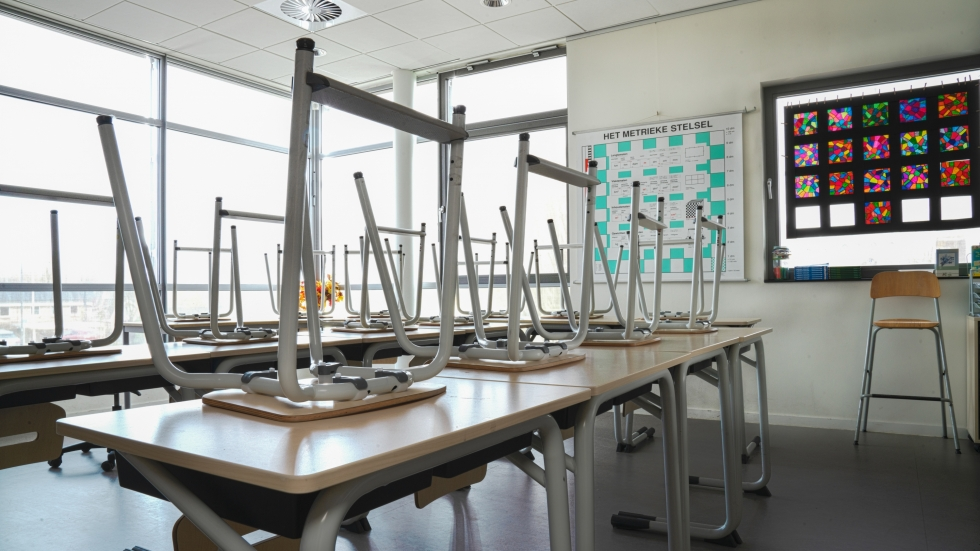An empty classroom with chairs stacked on the desks