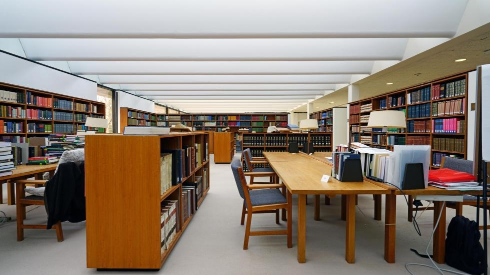 Empty tables surrounded by bookshelves inside a college library