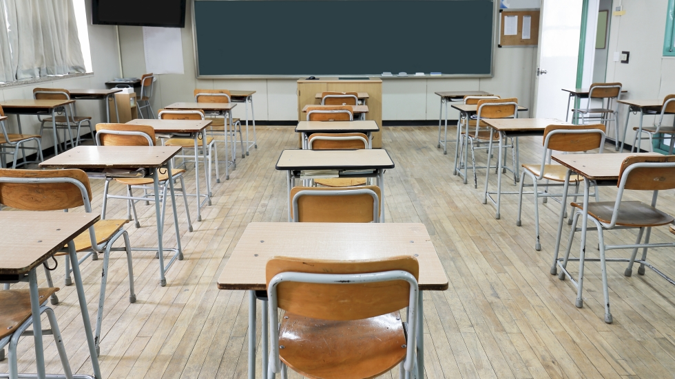 An empty classroom with lines of desks and chairs