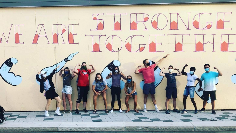 Summer on the Cuyahoga interns in front of We Are Stronger Together mural at the Van Aken District.
