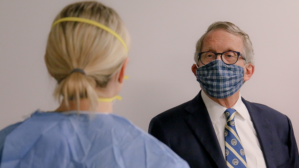 Ohio Gov. Mike DeWine wears a mask while talking with a medical professional
