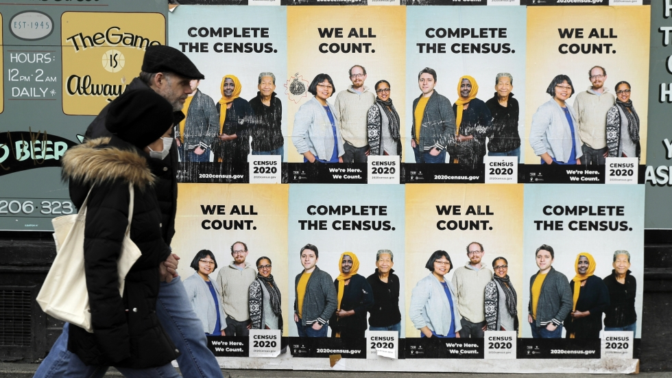 Two people walk past posters encouraging participation in the census.