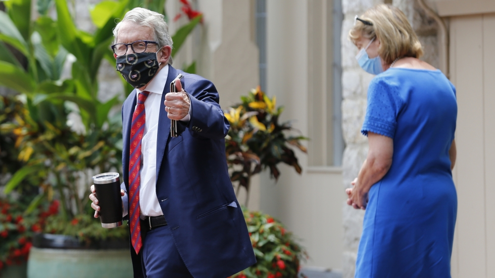 Gov. Mike DeWine, wearing a mask and giving a thumbs up with his wife, Fran, behind him.