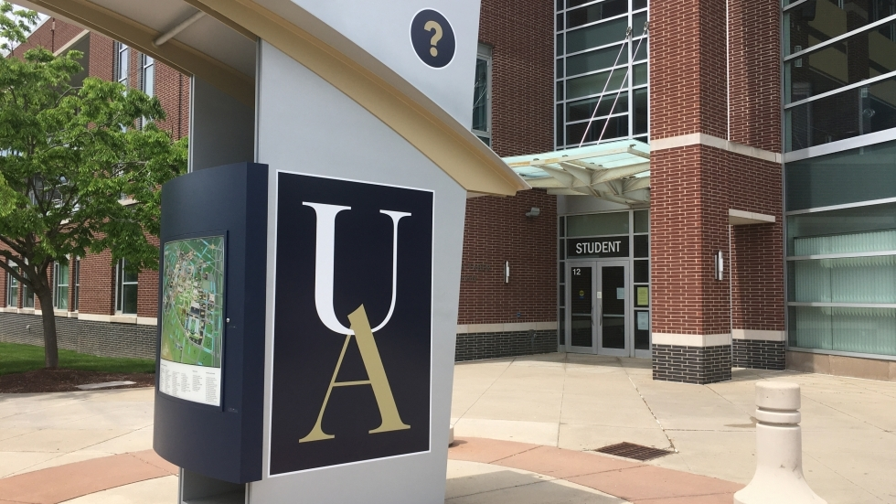 "A pillar at University of Akron with ""U A"" on the side and a map of the campus."