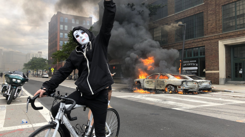 A masked person raises a fist in the air while astride a bicycle in front of burning vehicles in Downtown Cleveland on May 30, 2020