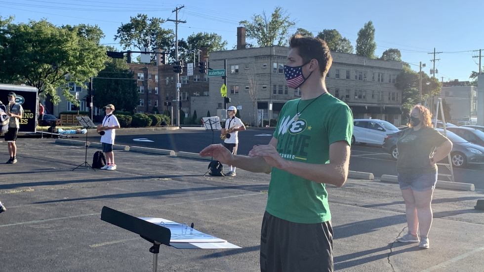 Richie Pokrywka, a senior at St. Edward High School,helps the marching band keep time as they practice in the high school's parking lot on August 18, 2020. [Anna Huntsman / ideastream]