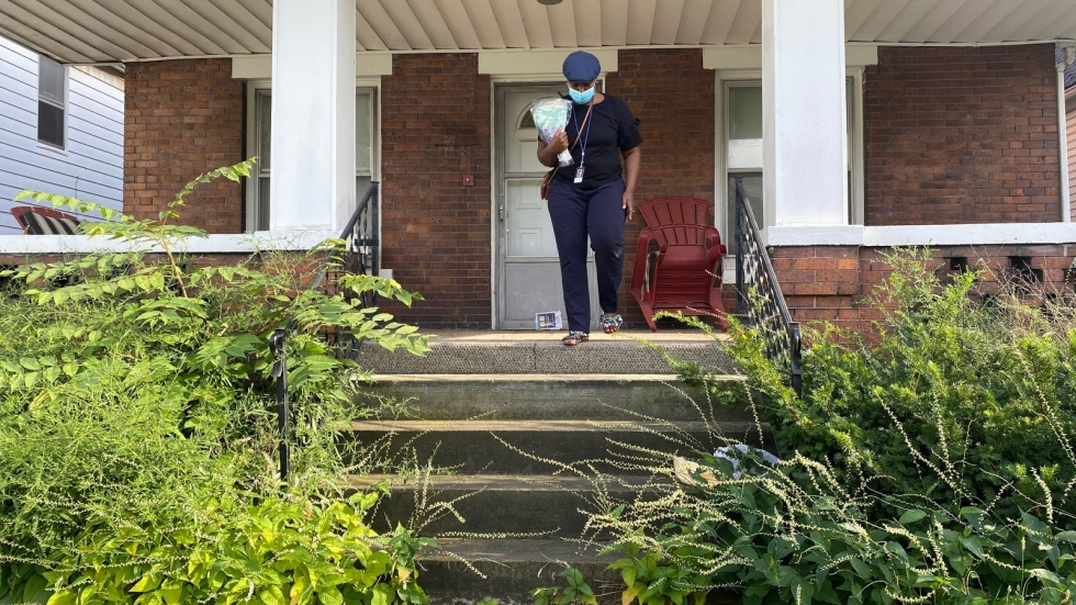 a woman wearing a mask on the front porch of a home in Cleveland's Slavic Village neighborhood