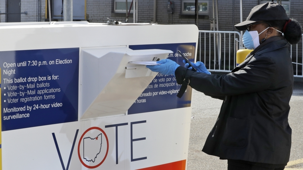 Marcia McCoy drops her ballot into a box outside the Cuyahoga County Board of Elections, Tuesday, April 28, 2020, in Cleveland, Ohio.