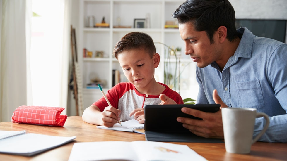 pre-teen boy sitting at dining table working with his dad
