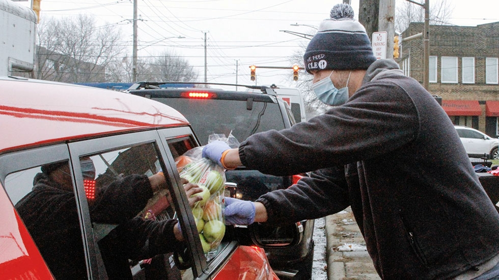 A food bank volunteer hands a bag of apples to someone through their car window.