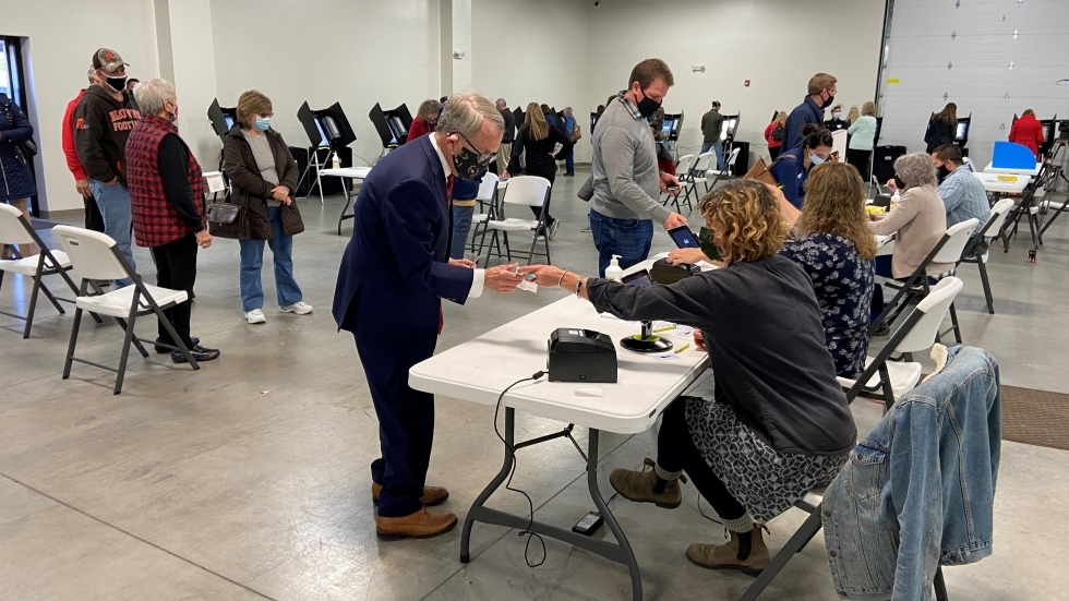 Ohio Gov. Mike DeWine checks in to vote at the Cedarland Event Center in Cedarville, after waiting in line to vote on Election Day.