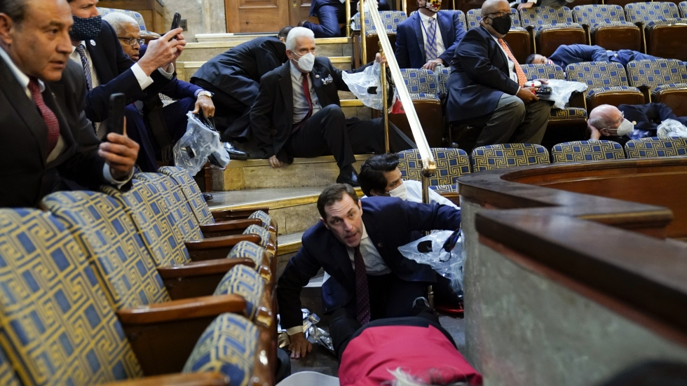 People shelter in the House gallery as protesters try to break into the House Chamber at the U.S. Capitol on Wednesday, Jan. 6, 2021, in Washington.
