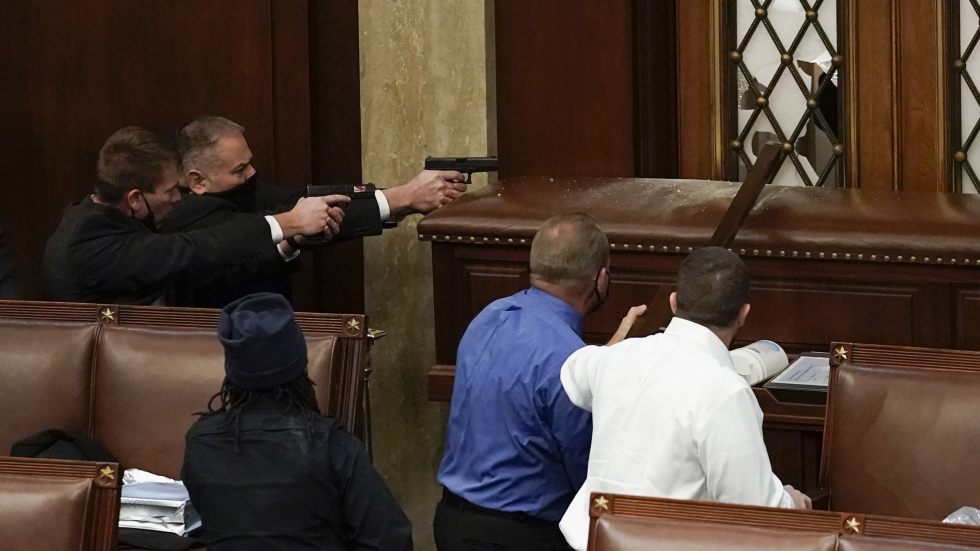 U.S. Capitol Police with guns drawn watch as protesters try to break into the House Chamber at the U.S. Capitol on Wednesday, Jan. 6, 2021, in Washington.