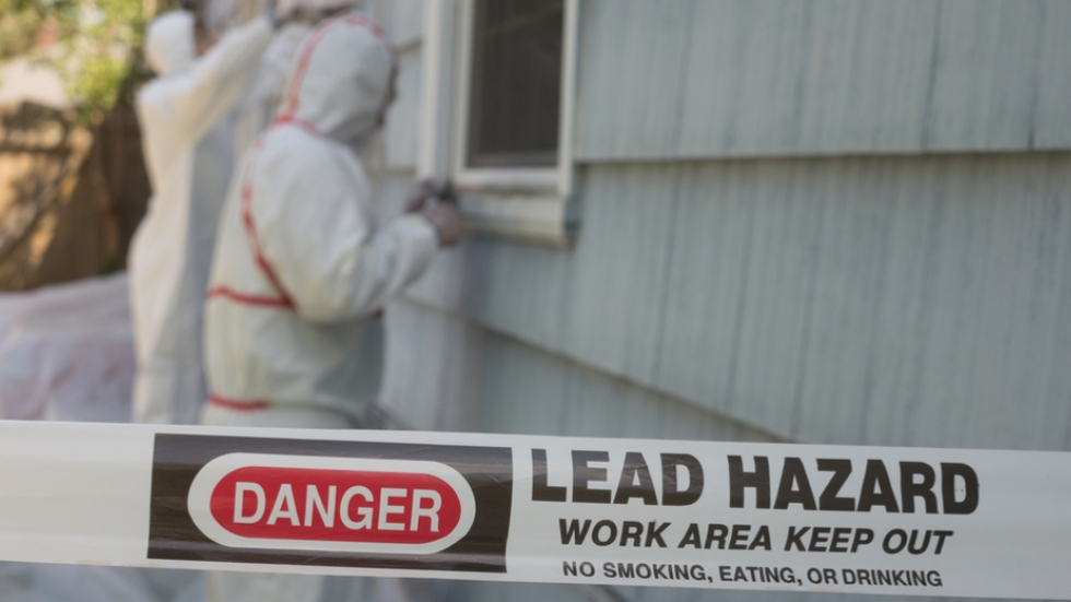 Two workers in protective gear remove lead paint from the outside of a house.