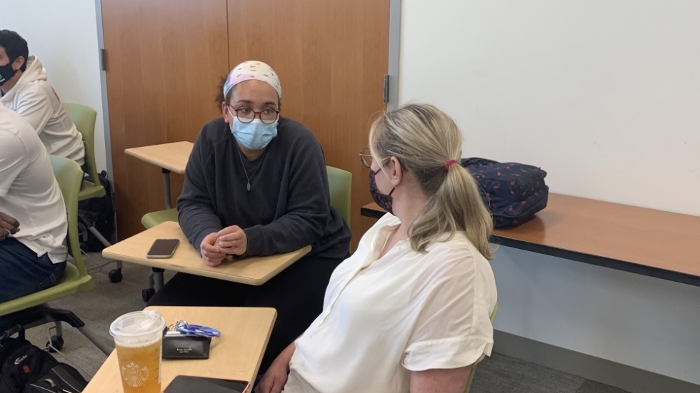 Tatiana Pascol (left) chats with another student, Kaitlyn Essig, before their Urban Health course at Cleveland State University begins on Sept. 30, 2021. Pascol, who is biracial, has received early assurance to medical school, and she plans to focus on emergency or surgery at NEOMED. [Anna Huntsman / Ideastream Public Media]