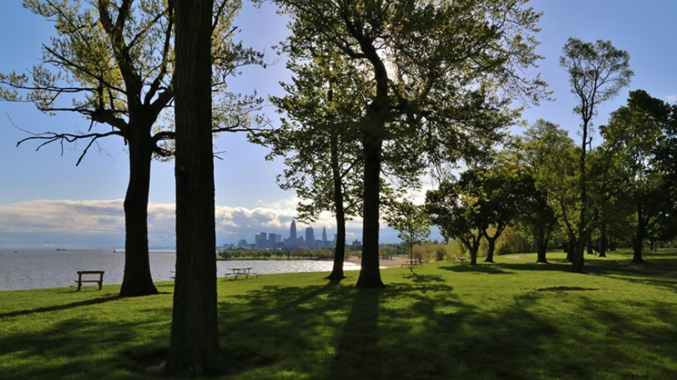 The Cleveland skyline peeks out from between trees at Edgewater Park on Lake Erie.