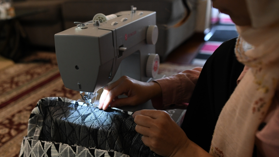 A woman sews a scarf as part of an adult sewing program supported by The Refugee Response.