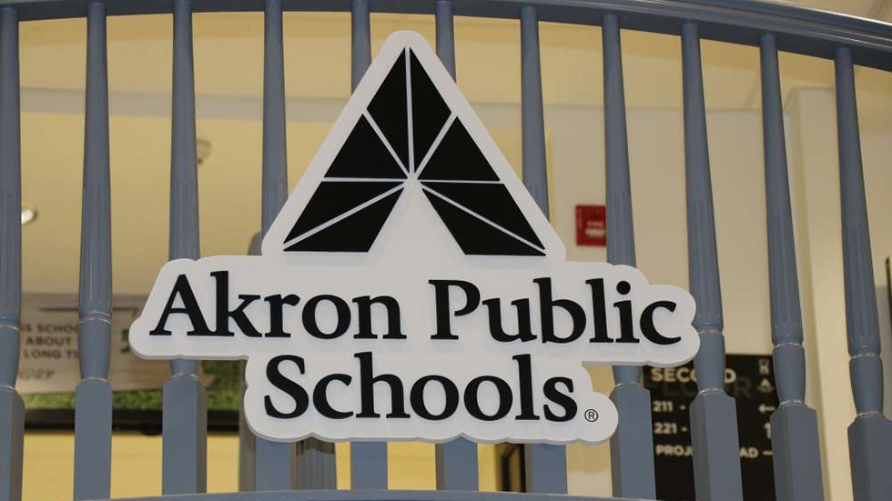 The Akron Public Schools logo on the railing of a staircase.