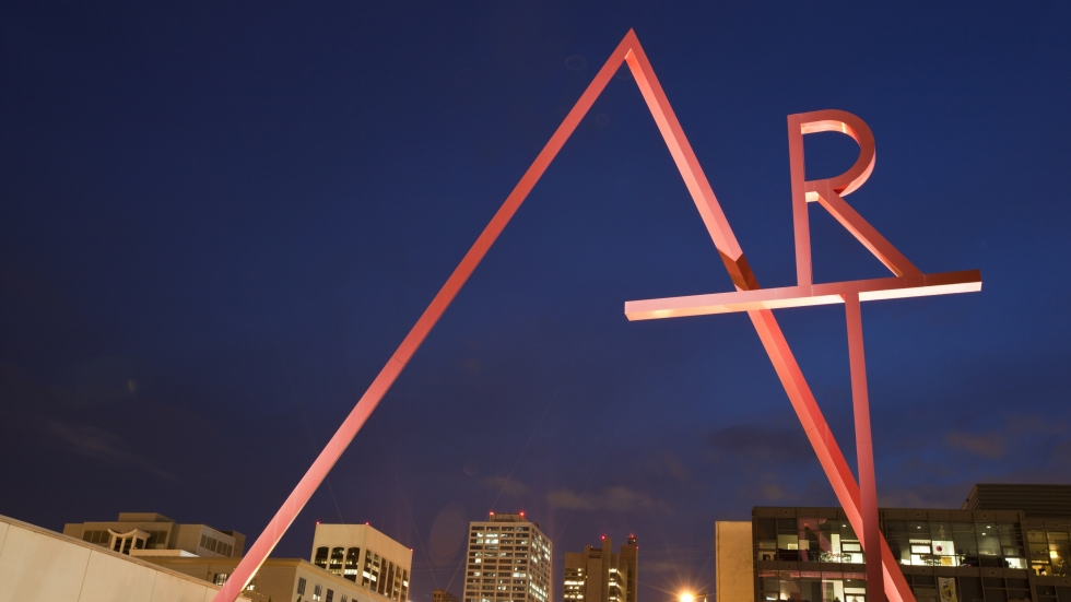The letters A,R and T are formed by red pipes outside of the Columbus School of Art and Design