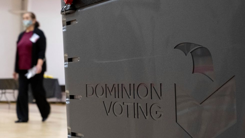 A worker passes a Dominion Voting ballot scanner while setting up a polling location at an elementary school in Gwinnett County, Ga., outside of Atlanta on Monday, Jan. 4, 2021, in advance of the Senate runoff election there. [Ben Gray / AP]
