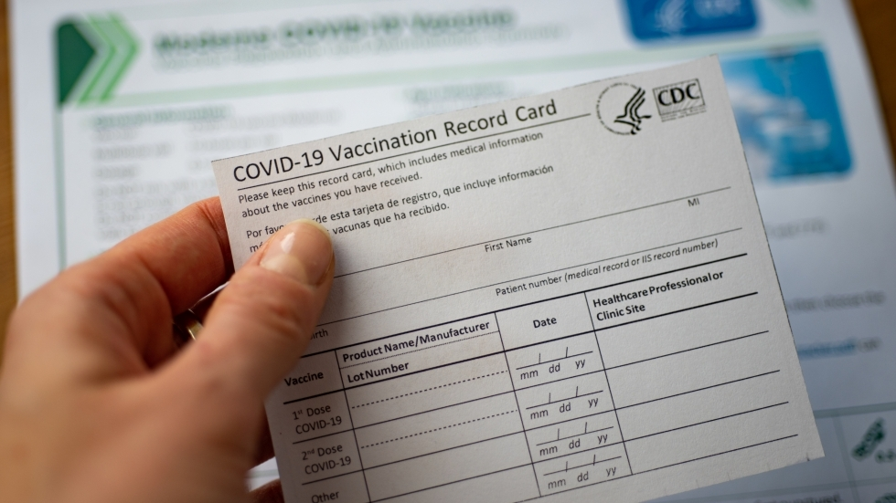A hand holds a CDC vaccination card