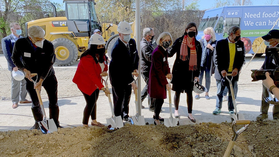 Members of the Greater Cleveland Food Bank expansion project push shovels into the dirt during a groundbreaking ceremony.