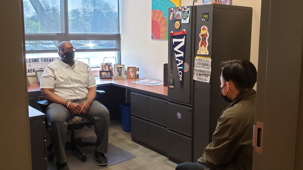 Rashawn McCraney (left) meets with a student in his office at Firestone Community Learning Center in Akron. School counselors like McCraney have had to adjust to meet students unique mental health challenges during the COVID-19 pandemic. [Daniel Sandy / Firestone Community Learning Center]]