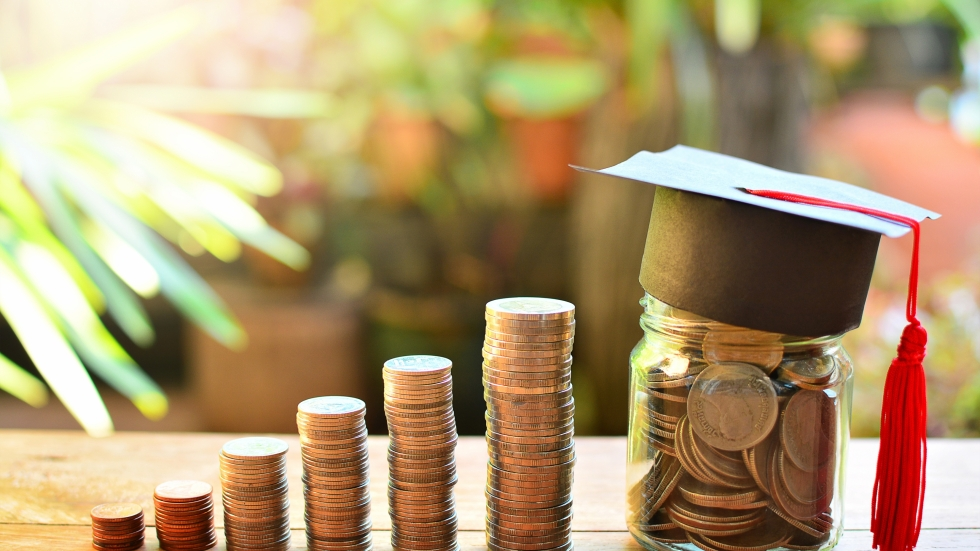 Stacks of coins rising to the height of a jar filled with coins topped with a graduation cap