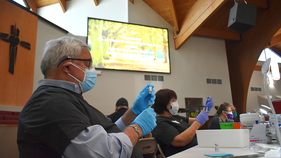 Several volunteers with Cleveland nonprofit Medworks prep vaccine doses at Affinity Missionary Baptist Church during a recent vaccine clinic. [Conor Morris / NEOSOJO]