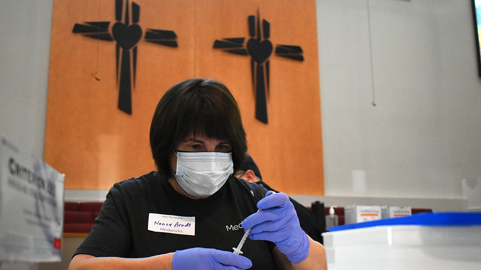 A volunteer with Cleveland nonprofit Medworks preps vaccine doses at Affinity Missionary Baptist Church during a recent vaccine clinic.