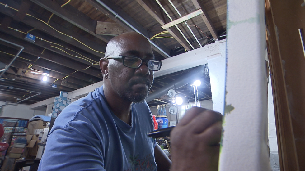Michelangelo Lovelace focuses on a painting detail in his Cudell studio.