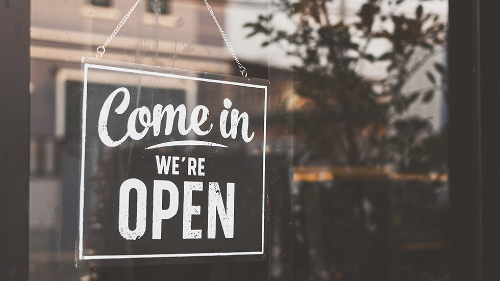 A sign in a window that reads 'come in, we're open.'