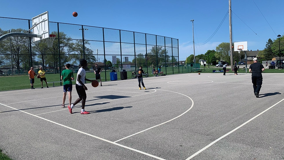 Several people gathered on a basketball court for a game.