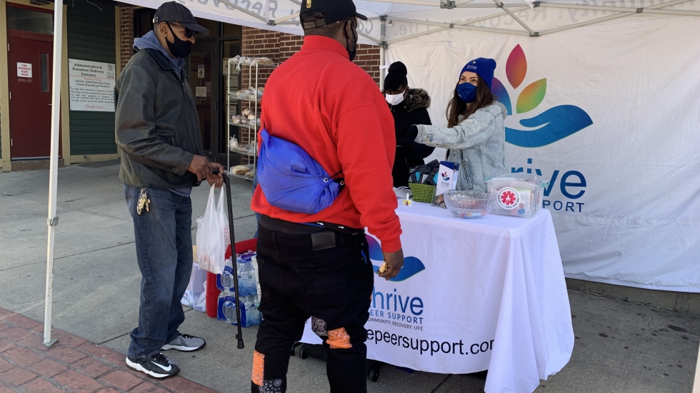 Ashley Rosser of Thrive hands a free naloxone kit to Tony Phillips. The kit also includes fentanyl test strips, food, water, and other resources so people can provide help to someone having an overdose. [Lisa Ryan / ideastream]