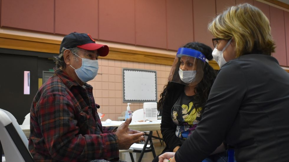 Mariano Collazo (left) asks questions about the vaccine while Jessica Centeno and Jennifer Sobrowski, with Neighborhood Family Practice, listen at a vaccine clinic at at La Sagrada Familia church in Cleveland, Ohio