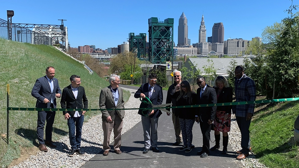 A row of people holding giant scissors and preparing to cut a green ribbon along a paved trail in Cleveland, Ohio..