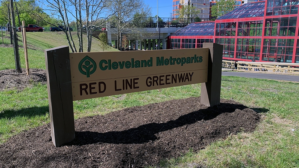 """A sign reading """"Cleveland Metroparks Red Line Greenway."""""""