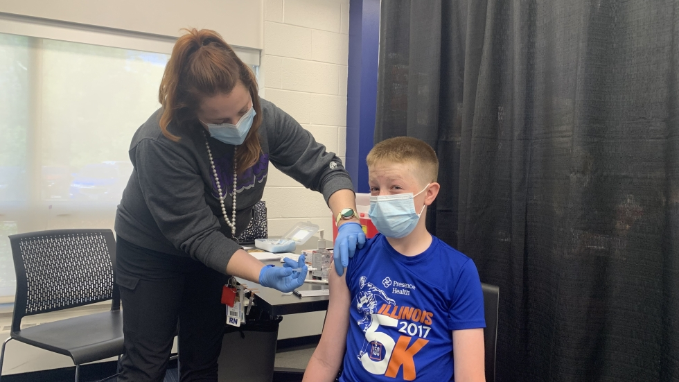 Tommy Wilds, a 13-year-old seventh grader at Edgewood Middle School in Wooster, flinches as he receives the first dose of the Pfizer COVID-19 vaccine during an in-school clinic Friday, May 14, 2021. Young teens aged 12 to 15 are now getting the shot across Northeast Ohio. [Anna Huntsman / ideastream]