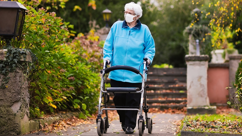 A woman walking along a brick path with a walker, wearing a bright blue jacket and a face mask.