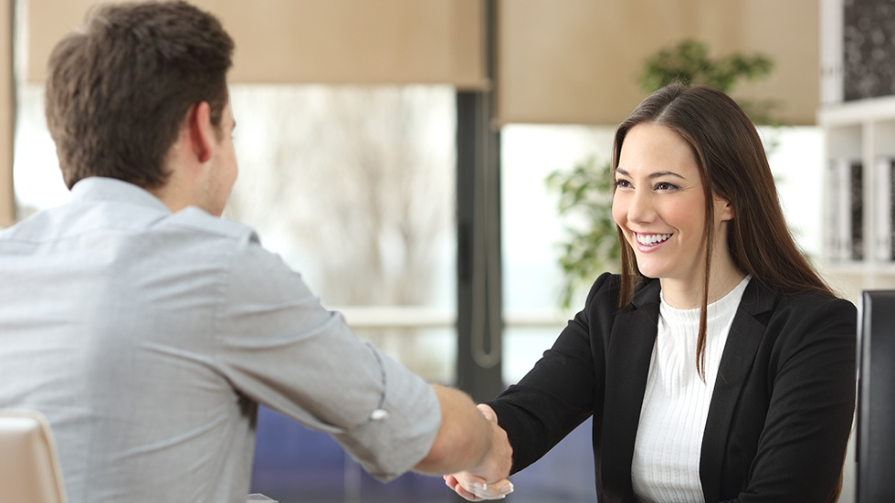 A woman shaking hands with a man whose back is to the camera.