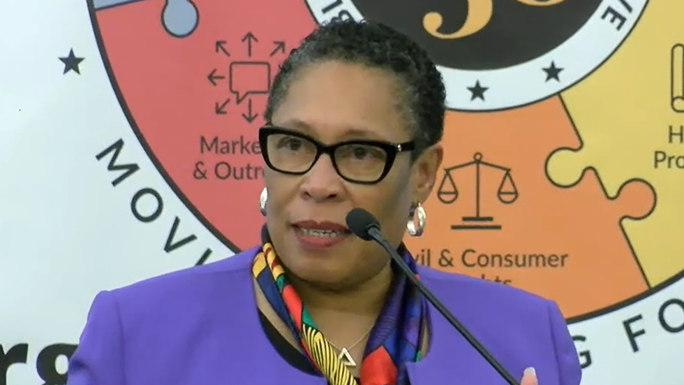 Marcia Fudge stands in front of the 3by30 graphic at Cleveland State University