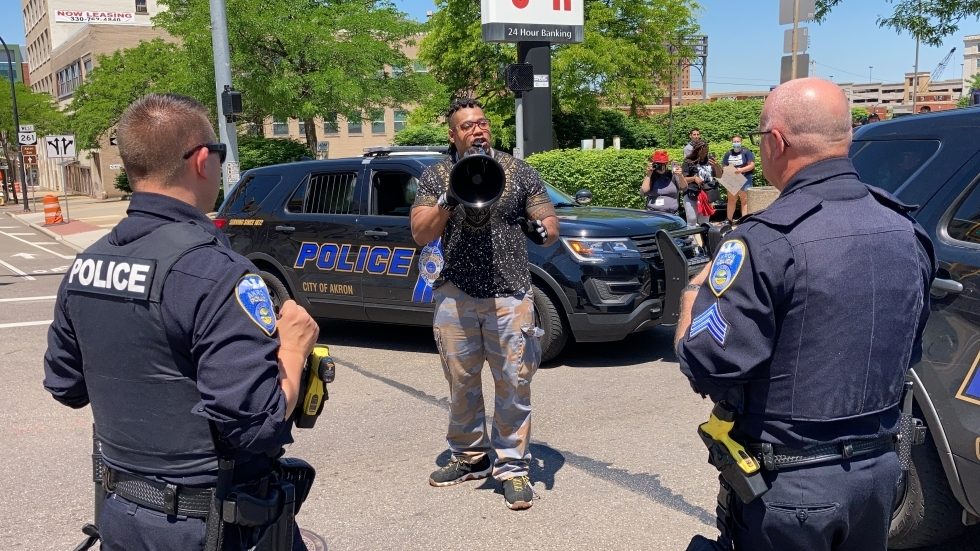 protestor in Akron flanked by uniformed police officers