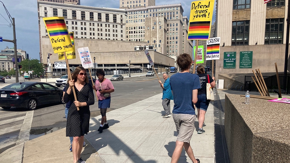 A group of people marching in a circle with signs calling for trans rights.