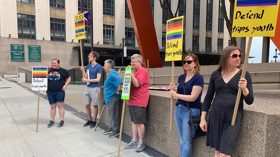 Six people standing in front of a wall holding signs in support of trans rights.