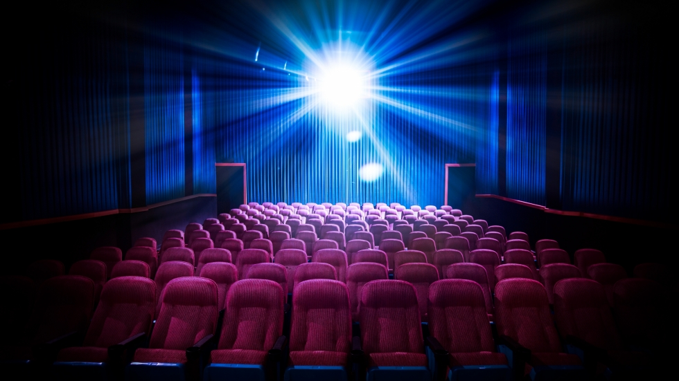 The light from a projector illuminates a theater of empty seats