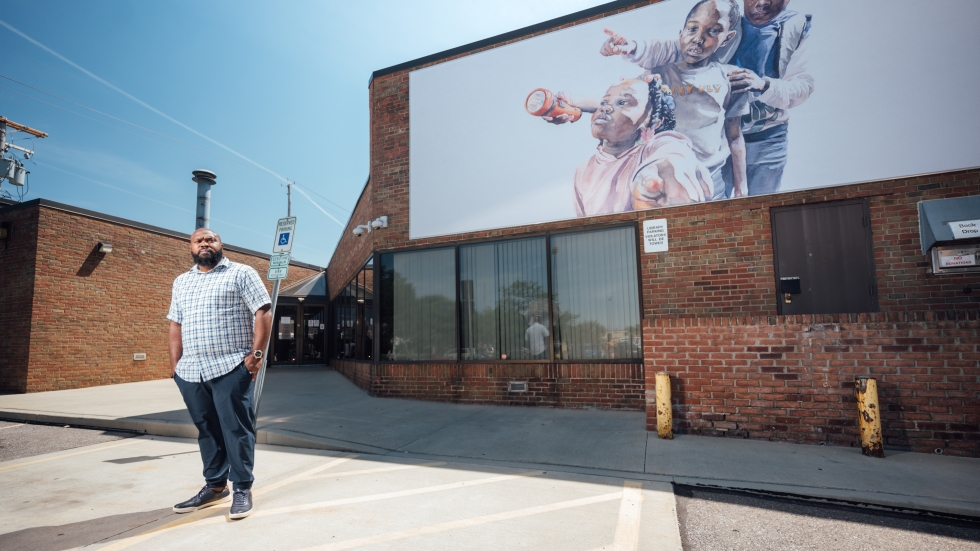 Artist Darius Steward at his new mural at the Lee-Harvard branch of the Cleveland Public Library [Cleveland Public Library]
