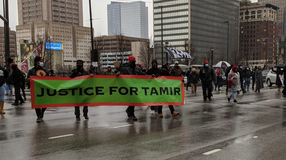 Demonstrators hold a green Justice for Tamir sign on a Cleveland city street