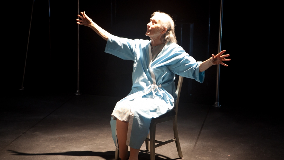 """Dorothy Silver sits in the spotlight of a barren stage, her arms outstretched, in the 2011 Beck Center production of """"Wings."""""""