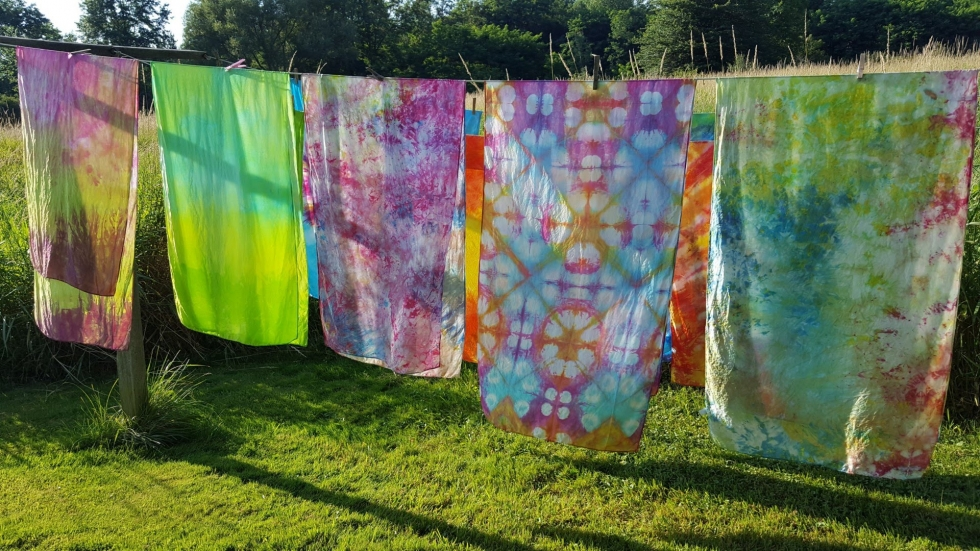 Colorful, dyed scarves hanging on a clothing line.